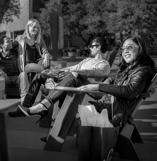 A group of friends sitting outside at a Sonesta exterior patio enjoying all of their perks from an upgrade to Travel Pass Elite.